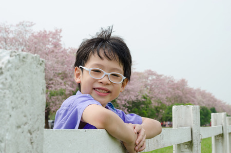 Asian boy smiling in park