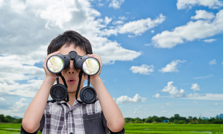 Young Asian boy using binoculars in field