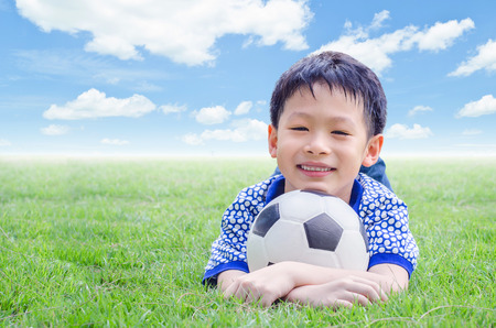 Little Asian boy smiles with his football on field