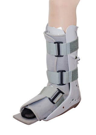 Woman leg with an ankle brace over white