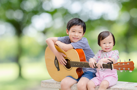 sings: Asian boy and his younger sister play guitar and sing in garden