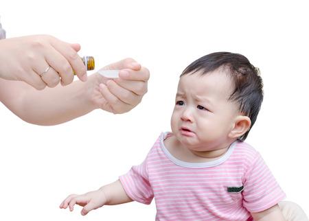 女性の白い背景の上の注ぐ薬スプーン手前で泣いている赤ちゃんの手します。