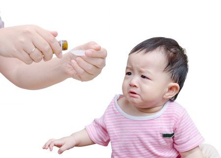 Woman's hands pouring medicine in a spoon foreground and crying baby over white background