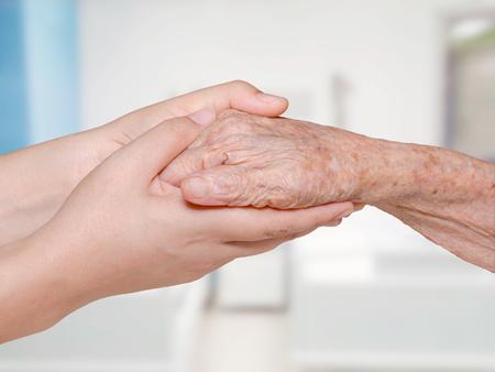retiring: Nurse holding olderly patient hand