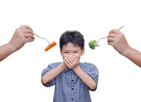 Asian boy close his mouth by hands because don't want to eat vegetables 스톡 콘텐츠