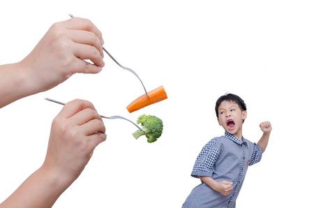 Little Asian boy run away from eating vegetables over white Foto de archivo