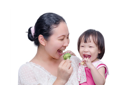 ni�a comiendo: Asia madre y su hija comer verduras sobre blanco