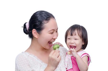 Aziatische moeder en haar dochter het eten van groenten over wit