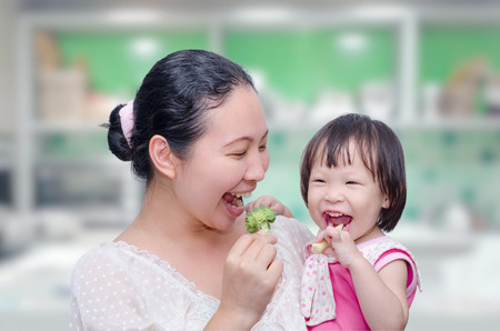 feed: Asian mother and her daughter eating vegetables