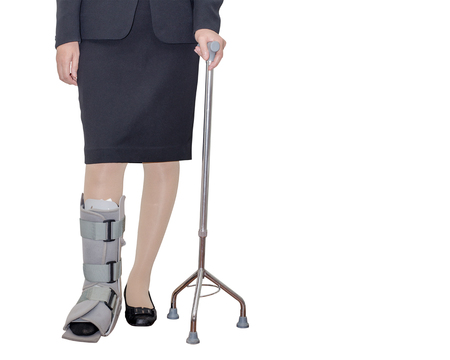 inconvenient: Business woman in suit with an ankle brace and stave