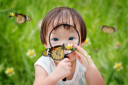 little girl with magnifying glass outdoors in the day time