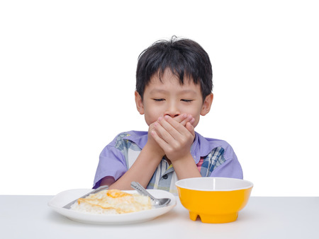 Asian child close his mouth by hand between having lunch Foto de archivo
