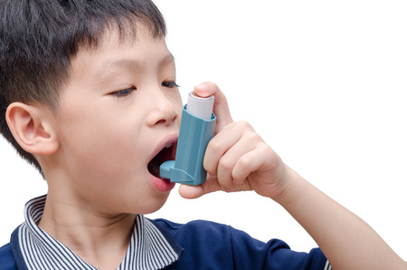 Asian boy using inhaler for asthma over white