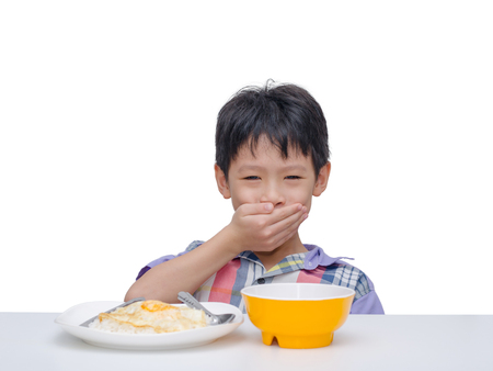 insipid: Asian child close his mouth by hand between having lunch Stock Photo