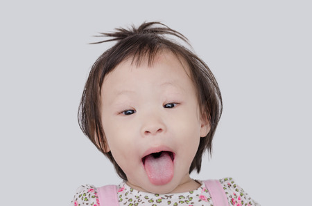 naughty child: Little Asian girl showing her tongue