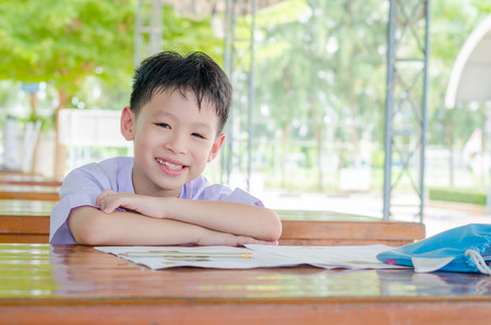 Asian schoolboy in uniform doing homework at school