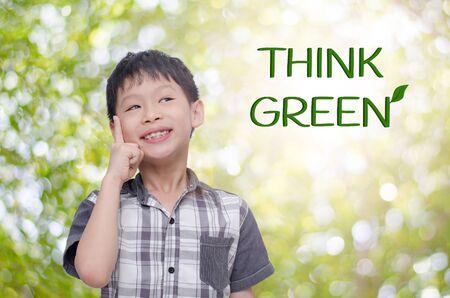 think green: Muchacho joven que piensa sobre el fondo verde, piense el verde concepto Foto de archivo