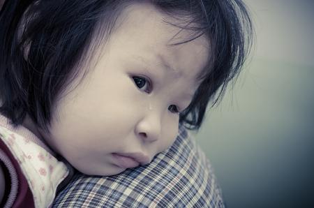 ojos llorando: Little girl crying on her parent shoulder with vintage filter Foto de archivo
