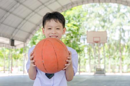 学校でバスケット ボールを保持しているほとんどのアジア学生