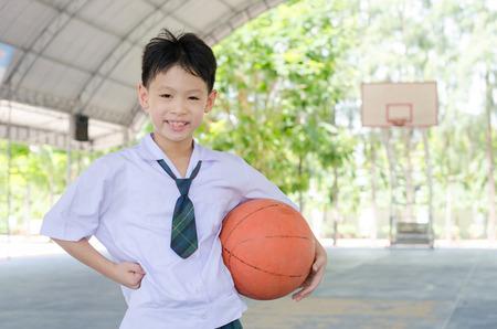 uniformes: Estudiante asiático pequeño que sostiene el baloncesto en la escuela Foto de archivo