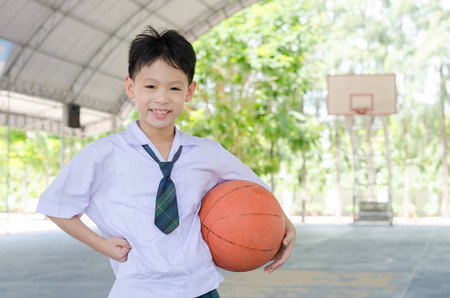 uniforms: Little Asian student holding basketball at school