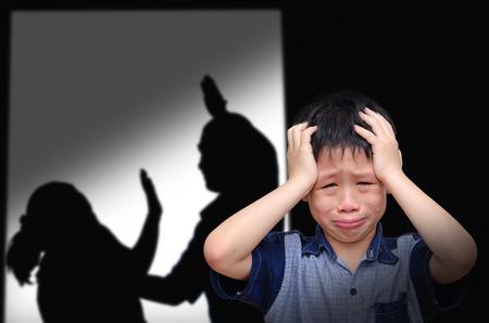 combate: Muchacho asi�tico llorando con su lucha de los padres en el fondo Foto de archivo