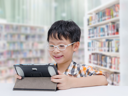 Asian boy student searching information by tablet computer in school library Stock Photo