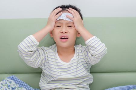 Little sick boy sitting on sofa Standard-Bild