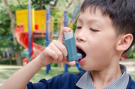inhaler: Asian boy using inhaler at playground