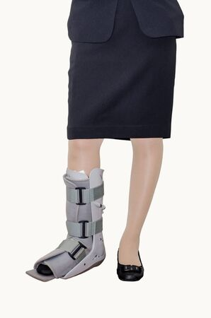 inconvenient: Business woman in suit with an ankle brace