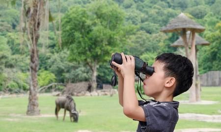 Young Asian boy using binoculars in open zoo