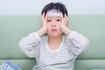 chory: Mały chłopiec chory siedzi na kanapie