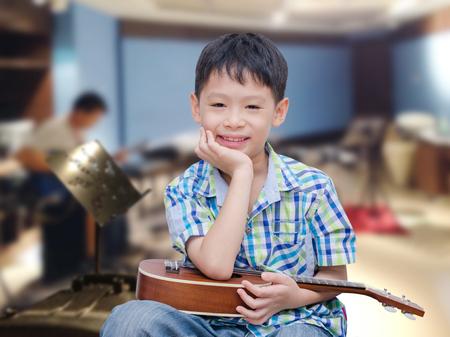 Young boy with ukulele in music school Stock Photo