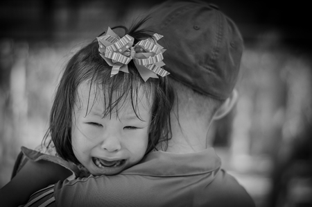 Little girl crying between stranger holding ,black and white color Stock Photo