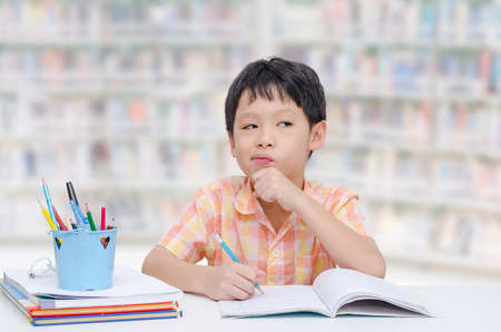 Little Asian boy thinking between doing homework Stock Photo