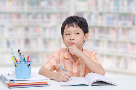 niños pensando: Poco muchacho asiático pensamiento entre hacer la tarea