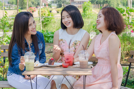 Three Asian girl eating cake and drink together at cafe