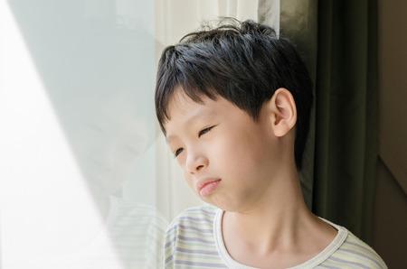 psicologia infantil: El muchacho asiático triste mirando por la ventana Foto de archivo