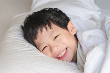 awake: Young Asian boy smiles after wake up on bed