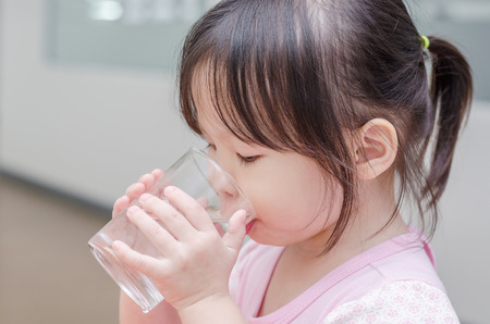 Little Asian girl drinking water from glass Stock Photo