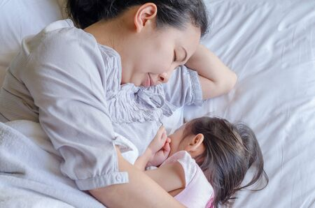 mother breast: Asian mother breast feeding her child on bed