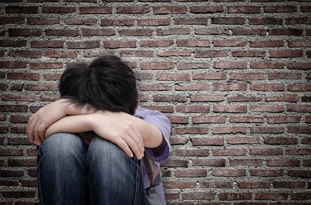 Ragazzino triste seduta sul pavimento sopra vecchio muro Archivio Fotografico
