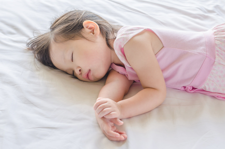 bebe enfermo: Niña asiática que duerme en la cama durante el día