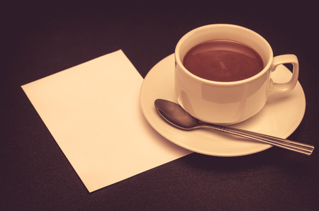 hedonism: coffee cup and paper note on table with vintage filter