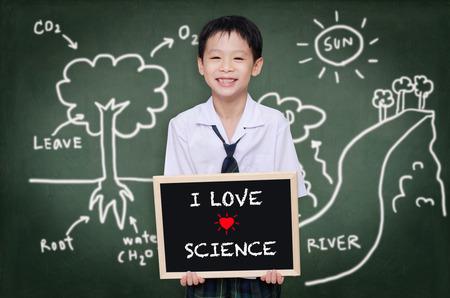 Asian schoolboy in uniform standing in front of chalkboard