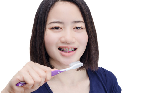 Young Asian girl with teeth brace over white background Stock Photo