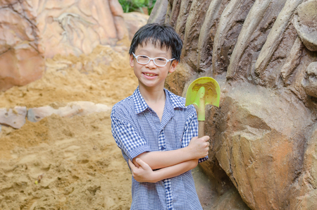 niños chinos: Joven asiático con una pala para cavar la arena Foto de archivo