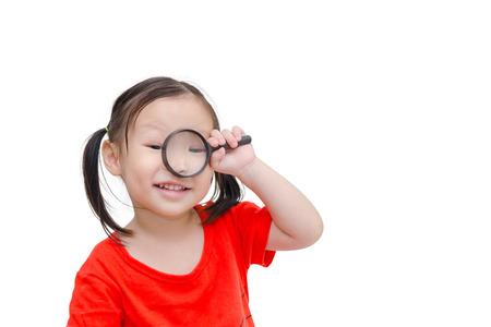 Little asian girl using magnifying glass over white