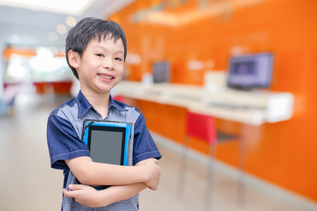 Young Asian boy holding tablet computer in computer room at school