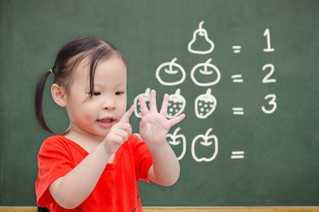 Little asian girl counting her finger in font of chalkboard